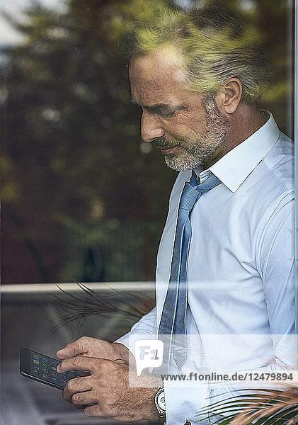 Mature man using smart phone behind window