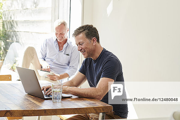 Mature couple using laptop and digital tablet