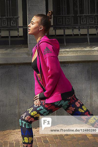 Junge Frau in rosa Jacke beim Stretching