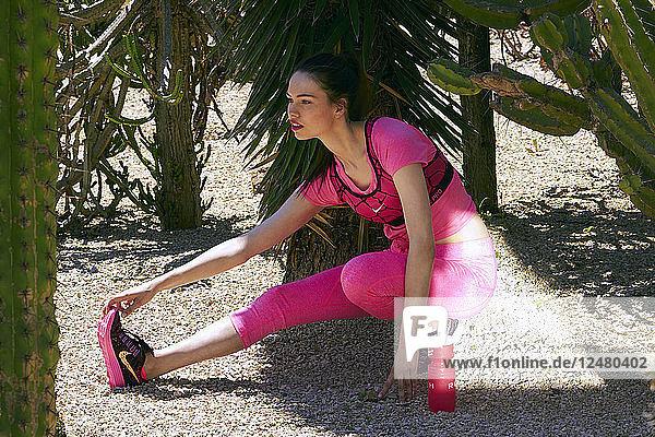 Junge Frau in rosa Sportkleidung beim Stretching