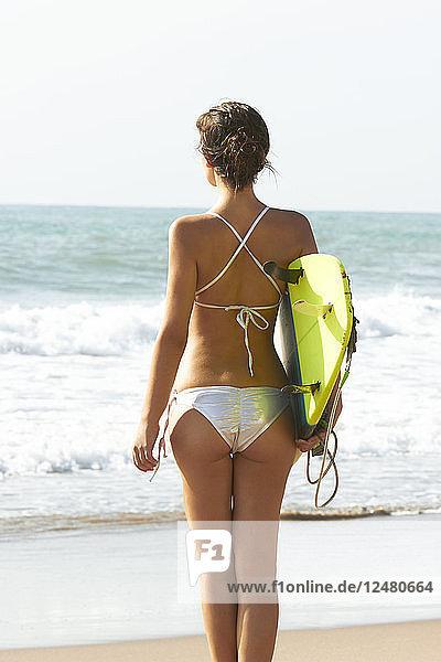 Young woman wearing bikini holding surfboard