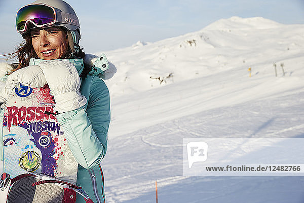 Woman in goggles and helmet with snowboard on mountain