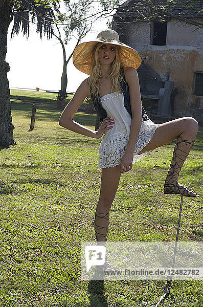 Young woman in field wearing sun hat and glamourous sandals