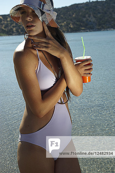Young woman in swimsuit and sun hat at beach