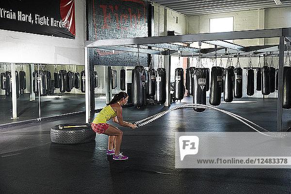 Frau trainiert mit Seilen im Fitnessstudio