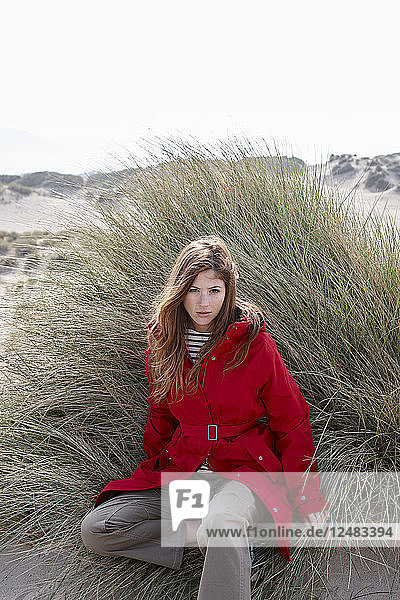 Young woman sitting in tussock grass on beach