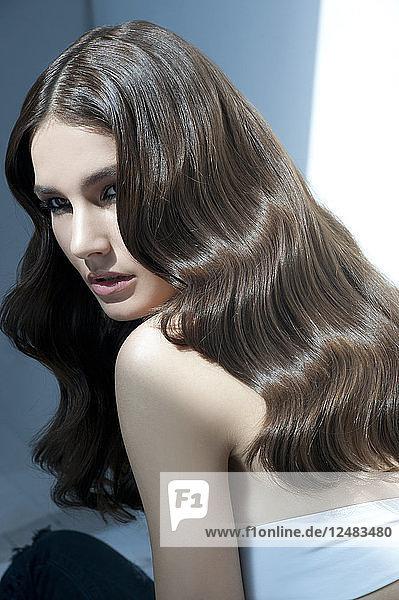 Porträt einer jungen Frau mit gewelltem Haar