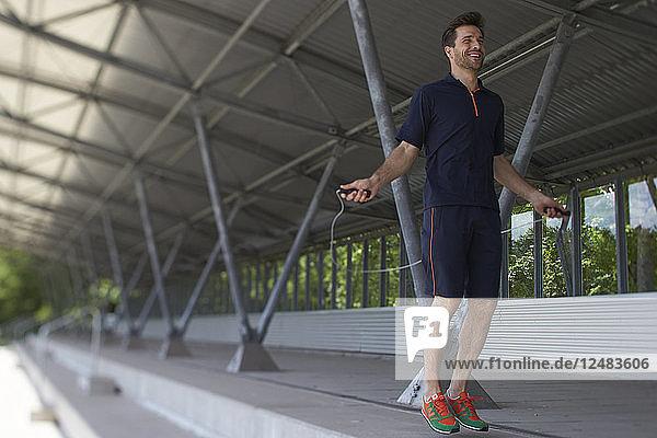 Junger Mann bindet Schnürsenkel auf der Tribüne