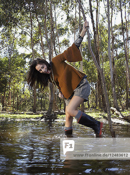 Young woman wading in river