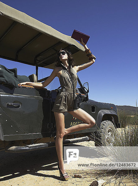Young woman posing on off road vehicle