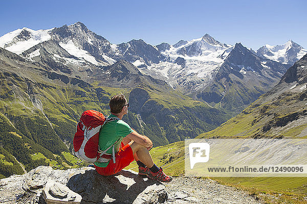 Hiker resting on rock and looking at view of mountains