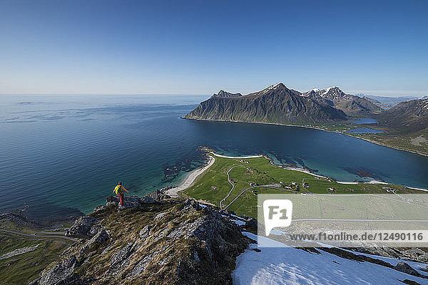 Female hiker enjoys view of beaches and coast from summit of Flakstadtind mountain peak  Flakstad??y  Lofoten Islands  Norway