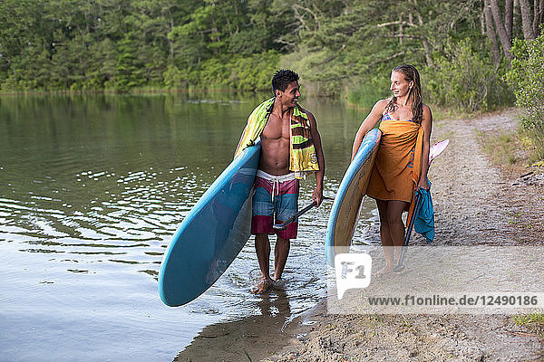 Young Couple Carrying Their Paddleboard Near Pond