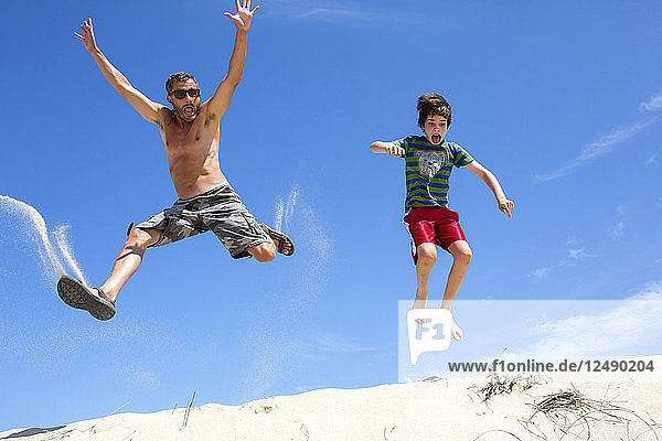A Man And Boy Jumping On Sand Dune In Provincetown