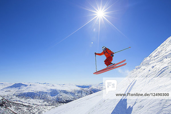 A male freerider in a red suit is jumping from a snow ridge. The sun is shining  the sky is blue. Myrkdalen in the Norwegian region of Flord is a secret powder ski paradise. The resort is close to the Voss area and counts an anual snowfall of up to 10 meters of snow.
