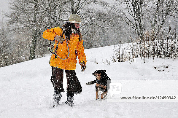 Woman Walking With Her Dog Walking In Snow