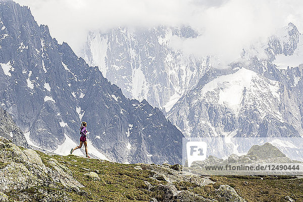 Girl trail running in Chamonix around the Chesery lake
