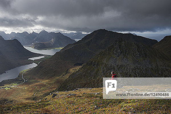 Female hiker on trail towards summit of Stornappstind (740m)  Flakstad??y  Lofoten Islands  Norway