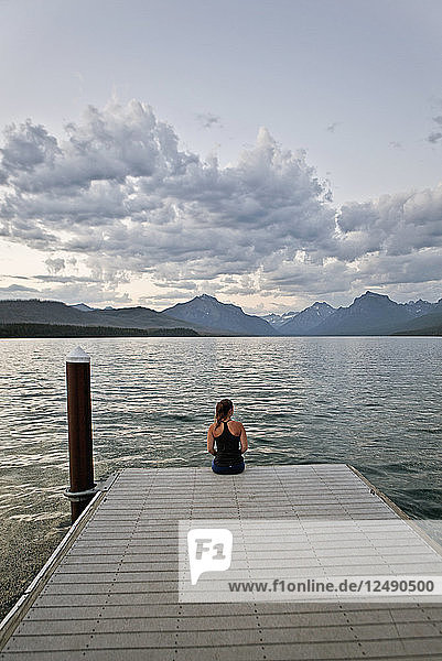 A young woman sits on the edge of a dock at sunset in Glacier National Park  Montana
