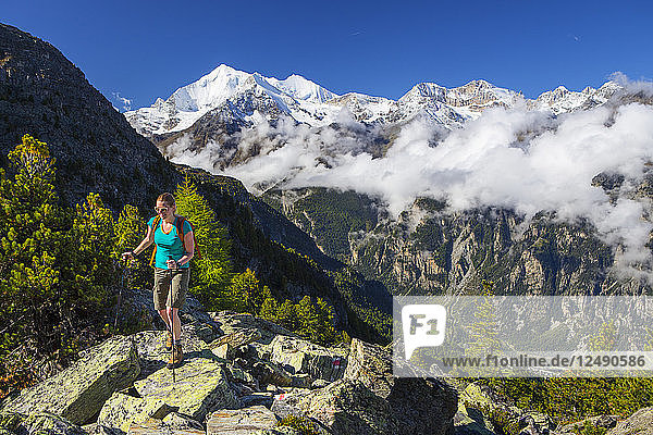 A female hiker on her way to the Wannihorn  a mountain peak in the Swiss Alps  close to Zermatt. In the background is the Weisshorn range. This region of Wallis is home to over 40 of 4000 meter peaks and a paradise for outdoor enthusiasts like climbers  hikers  mountainbikers  trailrunners and nature lovers.