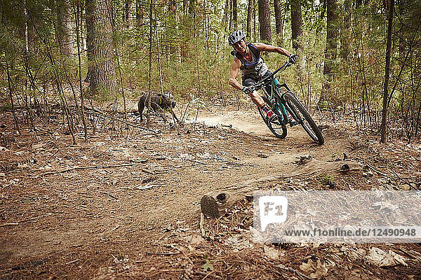 Woman Riding Mountain Bike On Dirt Track In Forest