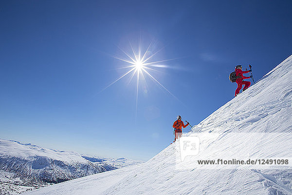 Two skiers are standing on a snowy mountain near the ski resort of Myrkdalen in Fjord  Norway. The sun is shining bright in the blue sky. With 5 meters of annual snowfall  all types of terrain and efficient ski lifts  you are all set for a wonderful ski holiday in Myrkdalen. Family-friendly Myrkdalen is located in Voss – only two hours from Bergen International Airport with direct flights from Copenhagen  Amsterdam and London. Myrkdalen is the largest ski resort in Western Norway - with family-friendly ski areas  slopes with all levels of difficulty  terrain parks  ski cross slopes and great off-piste terrain. Close to the ski resort are groomed cross country skiing slopes and great terrain for backcountry skiing. '