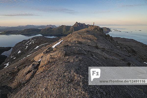 Female hiker stands on summit of Hestr?¶va mountain peak  Flakstad??y  Lofoten Islands  Norway