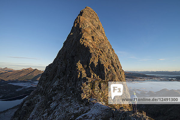 Female climber looks at route to summit of Reka mountain peak  Vester?•len  Norway