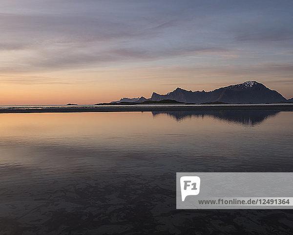 Midnight sun mountain reflection on Ytresand beach  Moskenes??y  Lofoten Islands  Norway