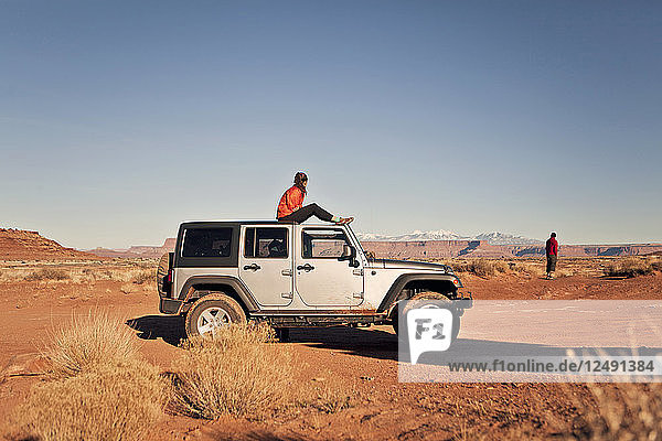 Two travelers take in the view from their Jeep while off roading in Canyonlands National Park