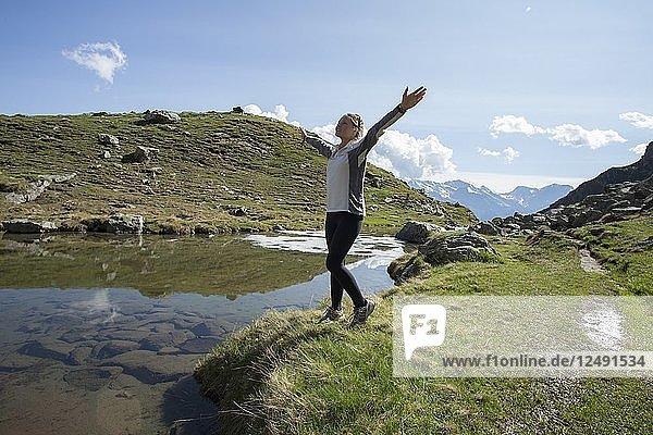 Young woman celebrates at edge of mtn lake