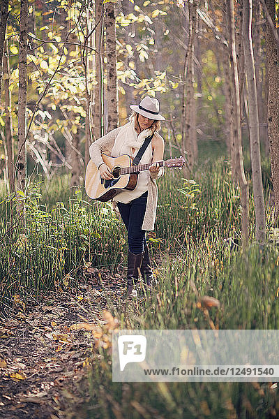 A young female folk singer poses in the woods with her guitar.