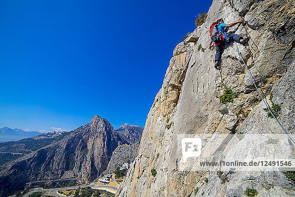 A man lead climbing a route at Sierra de Toix in Spain.