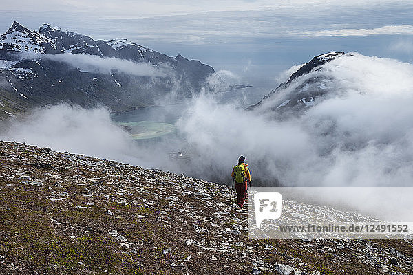 Female hiker hiking in cloudy weather while descending from summit of Volandstind mountain peak  Lofoten Islands  Norway