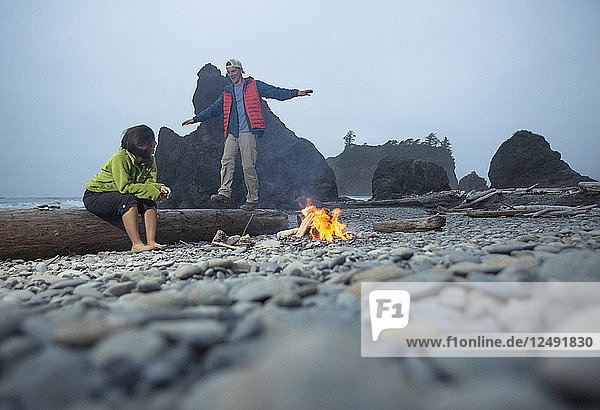 Two Hikers Enjoying Around A Campfire In The Pacific Northwest