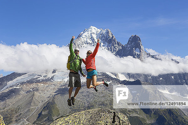 A male and female in colorful clothing are jumping happily in the air with the beautiful mountains of Chamonix in the French Alps in the background.