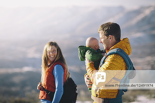 A young couple and their baby hike in the wintry mountains.