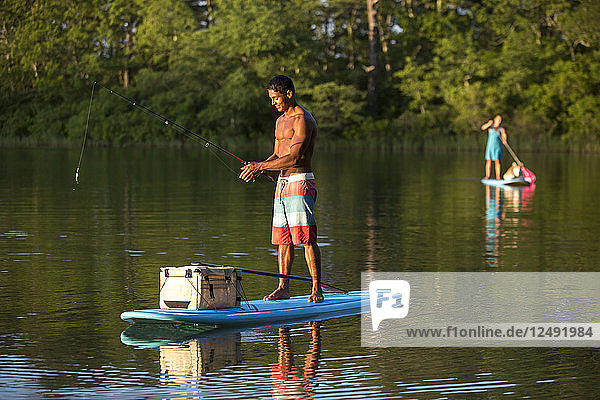 Young Happy Man Fly Fishing On A Paddleboard