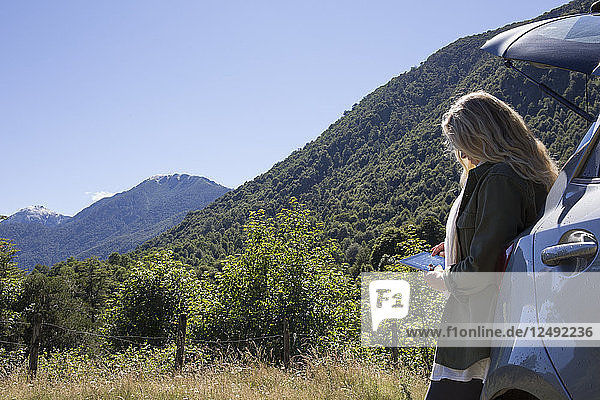 Woman uses digital tablet near trunk of car in mountains