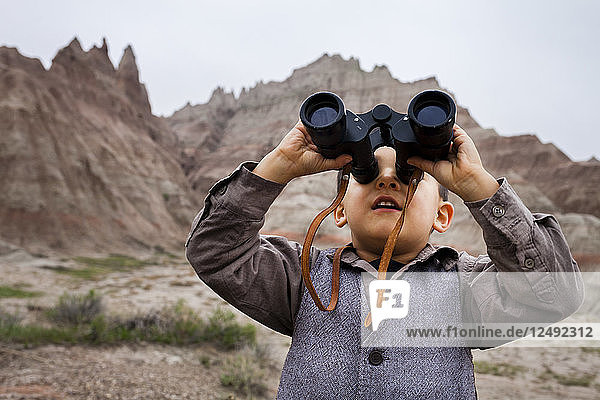 A 4 year old Japanese American boy dressed as an explorer with a hat and vest surveys the land (eroding rock formations of pinnacles and spires) with his binoculars in Badlands National Park,  South Dakota.