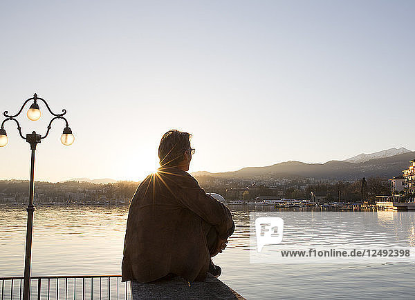 Man sits in park at sunset with lake and city behind