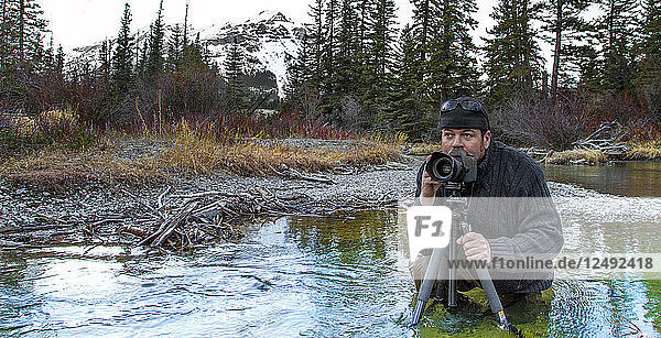Photographer composes with tripod in autumn