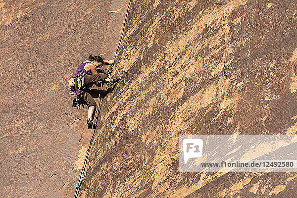 A woman rock climbing up a layback crack at a rock climbing area called The Wall in Indian Creek  Monticello  Utah.
