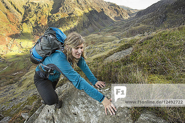 Female hiker arrives at mountain summit