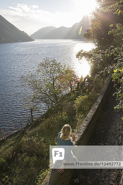 Woman relaxes on stone wall  looks across lake