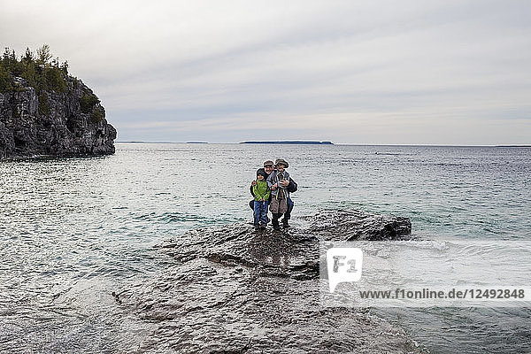 A family consisting of a 4 year old Japanese American  6 year old Japanese American boy and father stand on a rock in the shallows of Lake Huron  while exploring The Grotto of the Bruce Peninsula National Park  Ontario  Canada.