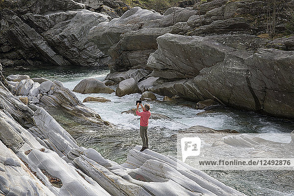 Man takes pic with digital tablet in river canyon