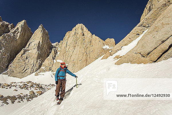 A 30 year-old woman in mountaineering clothes smiles as she descends a steep snow field with jagged granite peaks rising behind her.