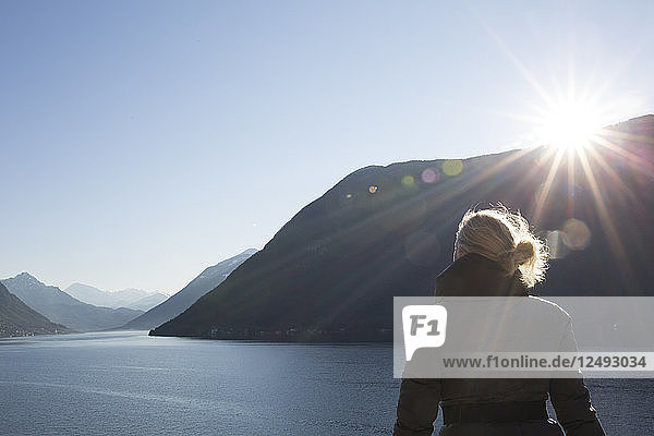 Mature woman looks out over lake and mountains