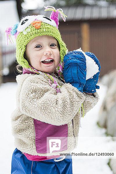 Smiling toddler girl gets ready to throw snowball toward camera  Lake Tahoe  California.